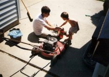 Luke teaching one of his mom's daycare kids how to change the oil in a lawn mower