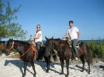 Katie and Luke horseback riding on the beach in Mexico