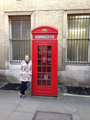 Katie standing by a phone booth in London